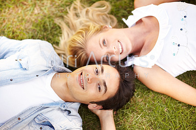 Young couple lying head to head on a grass patch