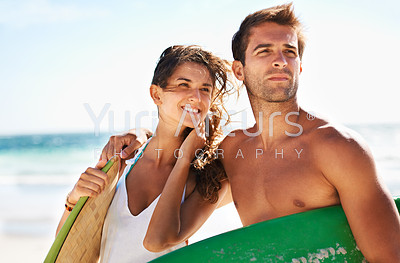Young couple looking on before heading out to surf - copyspace
