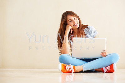 Full length of attractive young female sitting on the floor using laptop next to copyspace