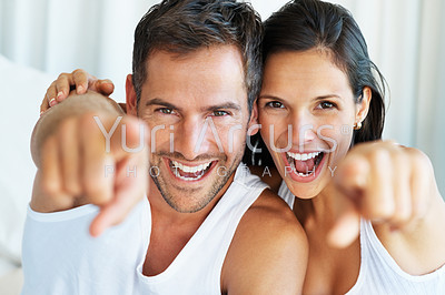 Portrait of happy couple pointing and laughing together