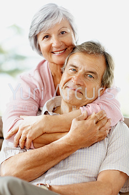 Portrait of a cute senior couple sitting together with arms around