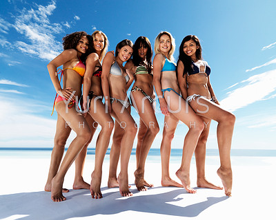 Full length of a happy group of females posing in bikini at the beach