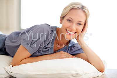 Beautiful young woman smiling while lying on the floor indoors
