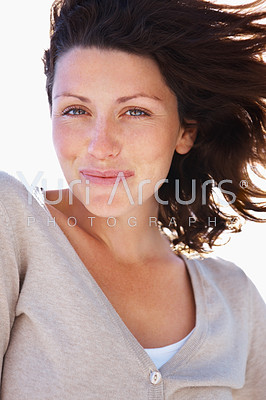Closeup portrait of a smiling young female with her hair being blown away by wind