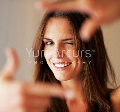 Young woman creating a frame with her hands and smiling at you
