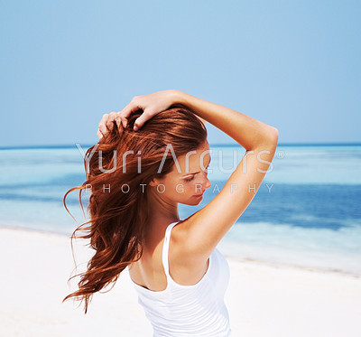 Beautiful young woman running her hands through her hair, on a bright beach with sea in the background