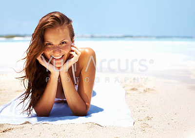 Portrait of young woman smiling beautifully at you while relaxing on beach alongside copyspace