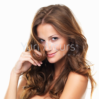 Portrait of a beautiful woman smiling at you while holding a strand of her hair to her face, isolated on white