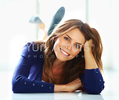 Portrait of relaxed young woman lying on the floor smiling engagingly at you - copyspace