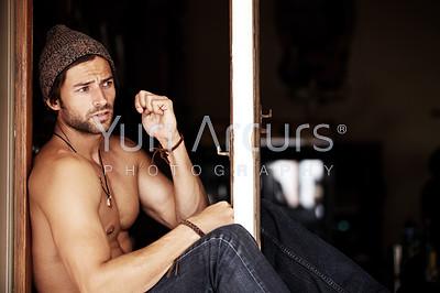 A sexy young man sitting shirtless on a windowsill