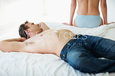 Portrait of a happy shirtless man lying on bed with wife in the background