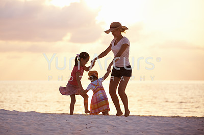 Portrait of happy mother with daughters playing on the beach